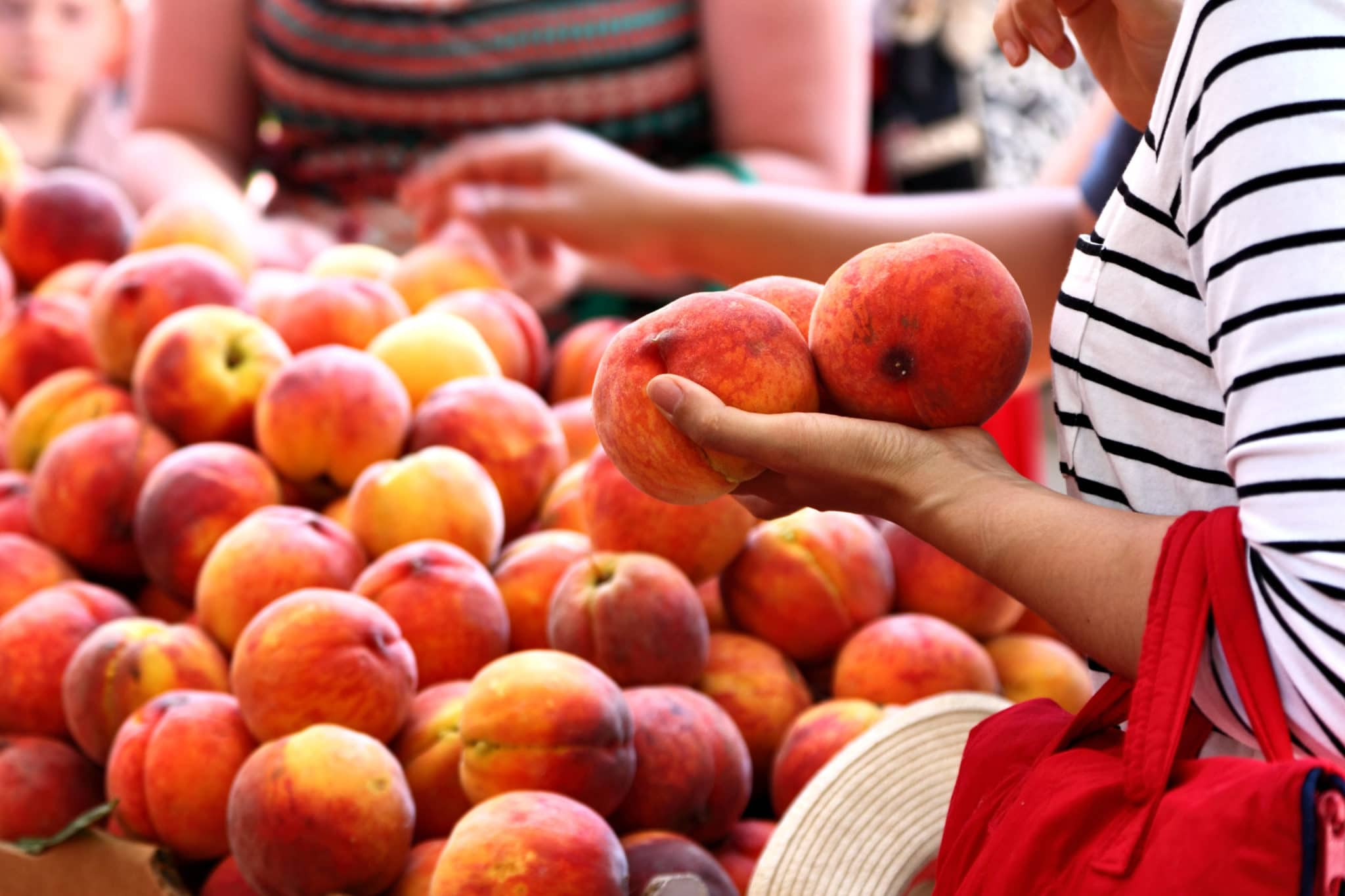 Woman shopping for peaches at the local farmers market