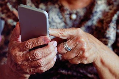 Elderly woman holding smart phone