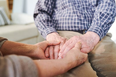 Aged supportife wife holding her mature husband by hands while supporting him in difficult period of life
