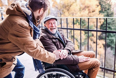 friendly visitor with man in wheelchair