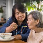 Caregiver daughter feeding mom