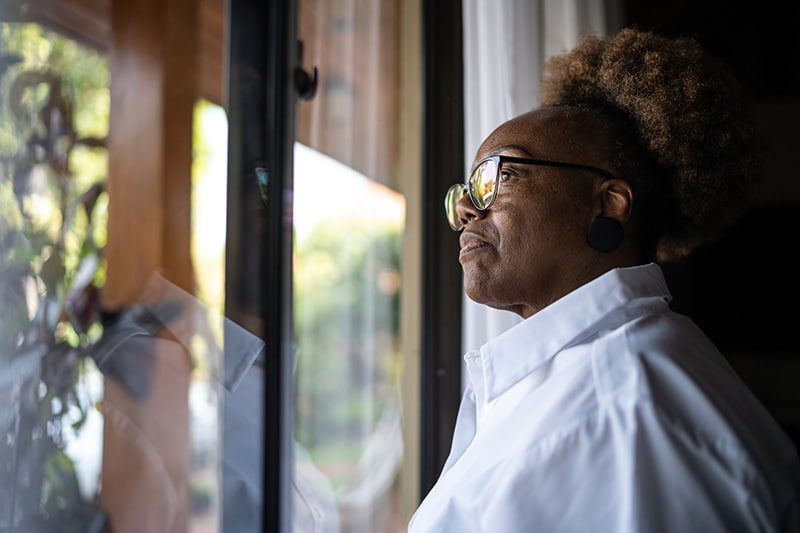 Isolated Senior Looking out Window at Neighborhood