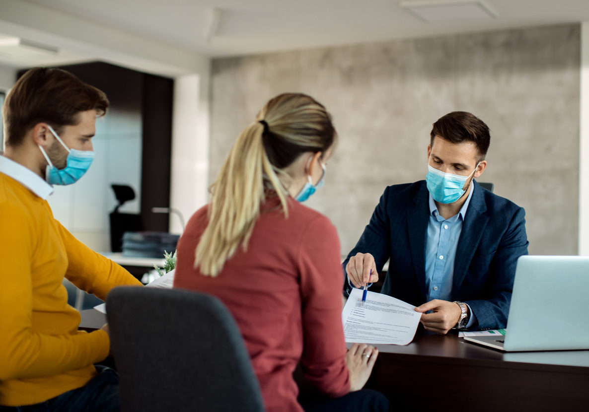 Financial planner meeting with couple with face masks during pandemic